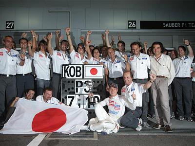 Камуи Кобаяси в окружении сотрудников Sauber рядом с боксами команды